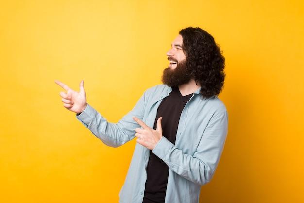 Fröhlicher hipster-mann mit langen lockigen haaren und bart, der auf gelbem hintergrund wegzeigt