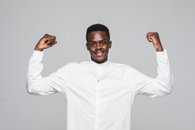 Fröhlicher hübscher afrikanischer kerl im kurzen weißen hemd, der ja geste macht, während er über das gewinnen aufgeregt ist. ekstatischer junger fan, der wurzeln schlägt und unterstützung ausdrückt.