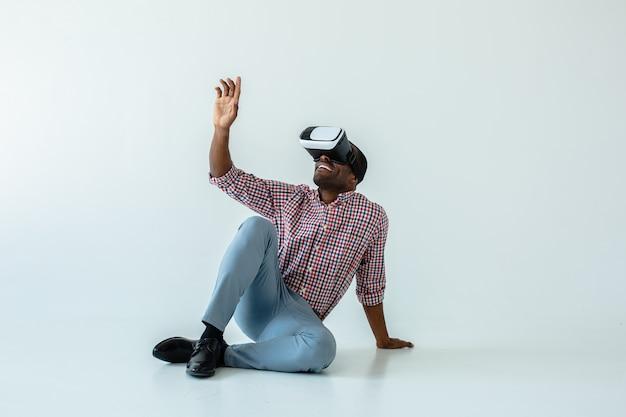 Fröhlicher hübscher afroamerikanischer mann, der auf dem boden sitzt, während vr-brille testend