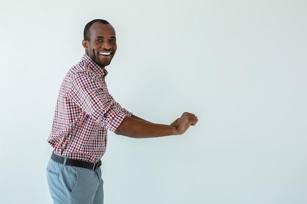 Fröhlicher hübscher afroamerikanischer mann, der den wagen gegen weiße wand bewegt