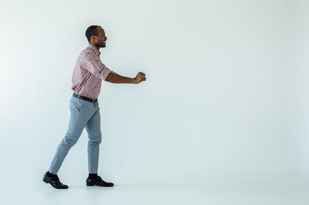 Fröhlicher hübscher afroamerikanischer mann, der einen einkaufswagen gegen weiße wand hält