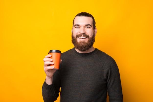 Fröhlicher hübscher bärtiger mann, der eine tasse kaffee trinkt, nehmen über gelb weg
