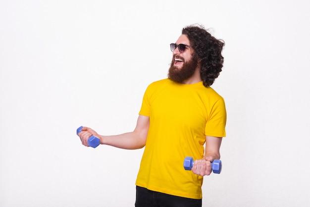Fröhlicher hübscher bärtiger mann mit langen lockigen haaren, die mit kleinen hanteln arbeiten