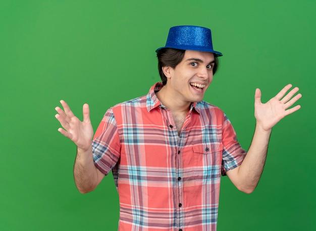 Fröhlicher hübscher kaukasischer mann mit blauem partyhut hält die hände offen