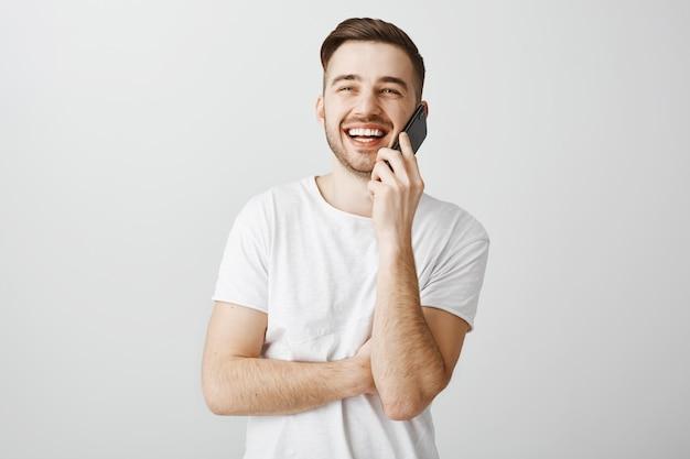 Fröhlicher hübscher kerl, der am telefon spricht und freund anruft