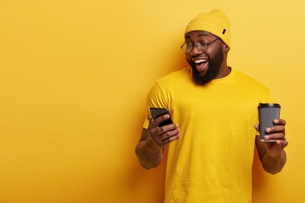 Fröhlicher hübscher kerl mit brille, die mit seinem telefon aufwirft