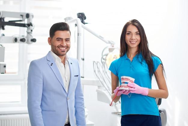 Fröhlicher hübscher männlicher patient lächelnd posiert mit seinem zahnarzt an der klinik service freundlich hilfsbereit facharzt personal gesundheitstermin professionalität beruf job menschen.