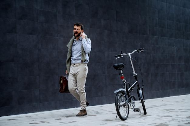 Fröhlicher hübscher modischer kaukasischer geschäftsmann, der musik hört, singt und aktentasche hält, während er zur arbeit geht. neben ihm steht fahrrad. im hintergrund ist graue wand.