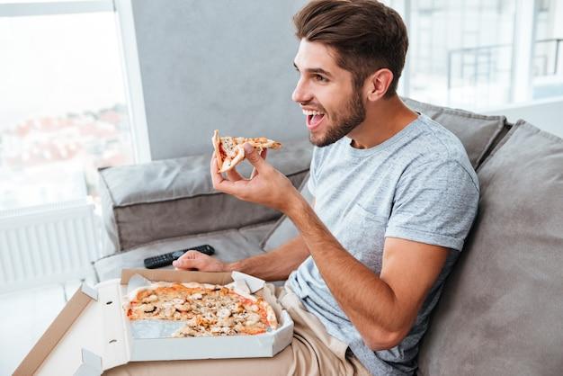 Fröhlicher hungriger junger mann, der pizza isst, während er auf sofa sitzt und fernsieht.