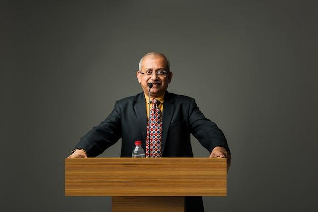 Fröhlicher indischer asiatischer gutaussehender leitender geschäftsmann, der mit mikrofon am podium im büro oder auditorium spricht und etwas präsentiert