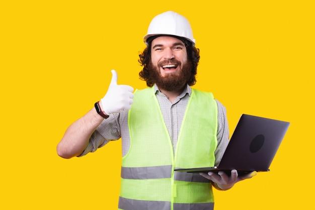 Fröhlicher ingenieurmann, der helm trägt und laptop hält und daumen oben zeigt