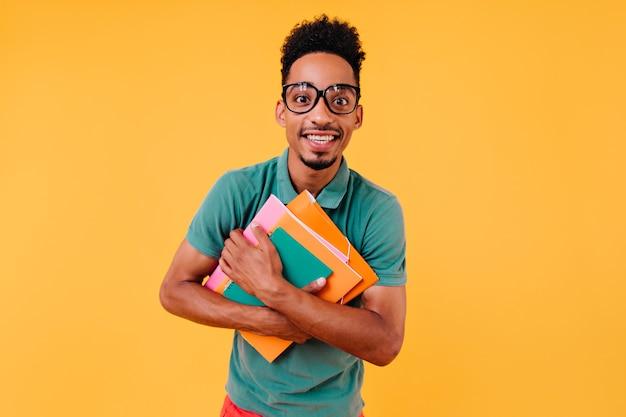 Fröhlicher internationaler student, der nach dem unterricht aufwirft. interessierter kluger junge in gläsern, die bücher halten.