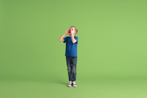 Fröhlicher junge, der an grünen wandgefühlen spielt und spaß hat