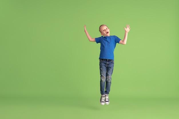 Fröhlicher junge, der an grüner studiowand spielt und spaß hat