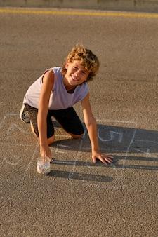 Fröhlicher junge, der auf asphaltboden zeichnet