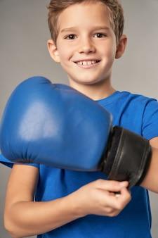 Fröhlicher junge, der boxhandschuhe vor grauem hintergrund anzieht