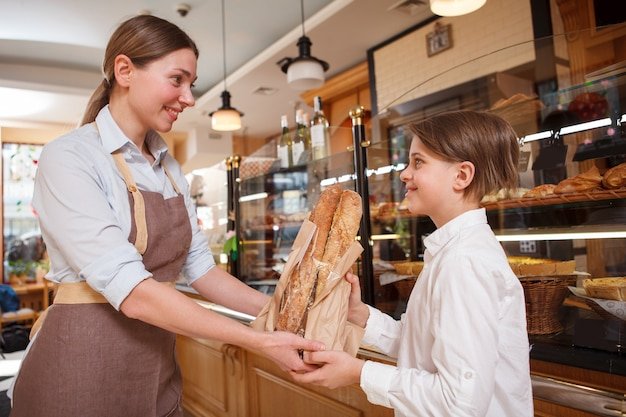 Fröhlicher junge, der brot von freundlicher bäckerin am örtlichen brotladen kauft