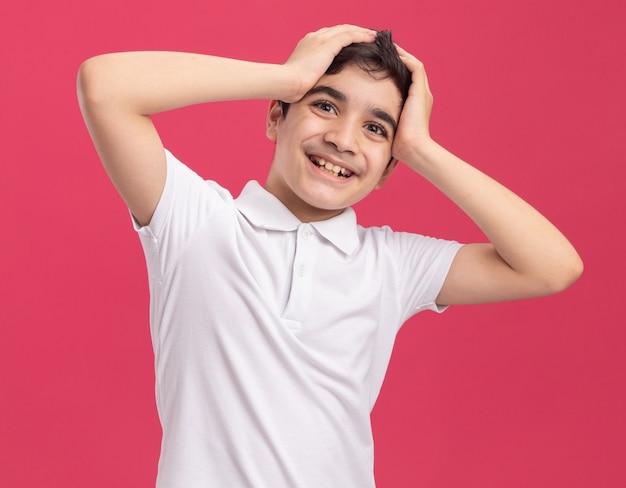 Fröhlicher junge, der die hände auf den kopf legt und nach vorne auf rosa wand schaut?