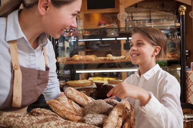 Fröhlicher junge, der frisches brot von der bäckerin kauft