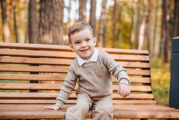 Fröhlicher junge, der im herbst auf einer bank im park sitzt