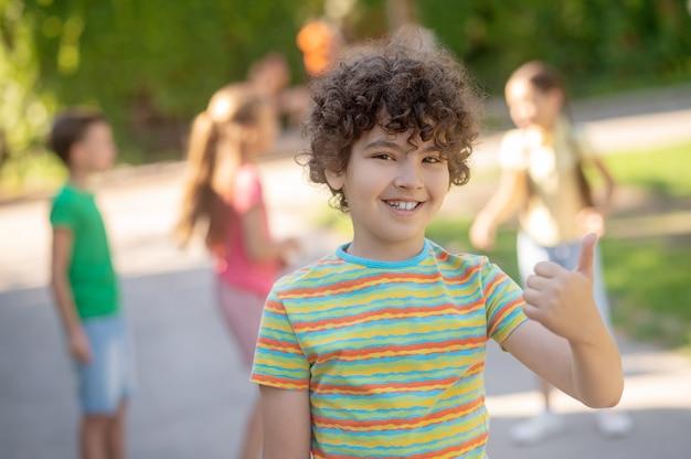 Fröhlicher junge, der im park eine gute geste zeigt