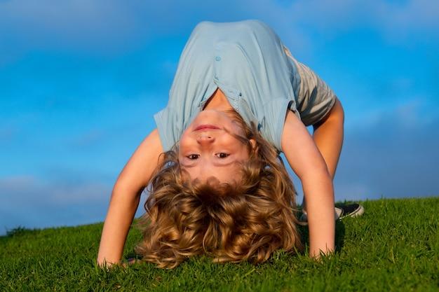 Fröhlicher junge, der im sommersonnenschein einen kopfstand auf dem gras macht lustiges glückliches kleines kind, das auf...