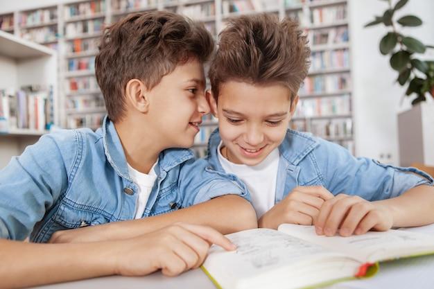 Fröhlicher junge, der seinem zwillingsbruder leise zuflüstert, während er zusammen in der bibliothek studiert