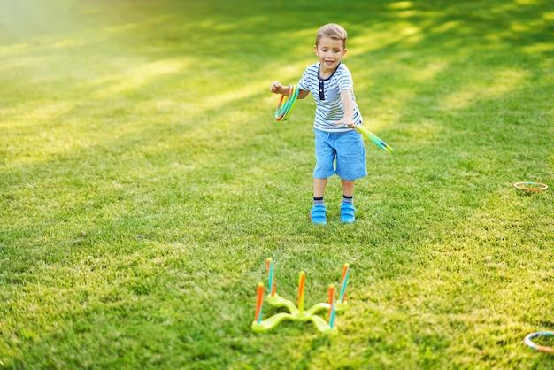 Fröhlicher junge, der spaß beim spielen im freien hat