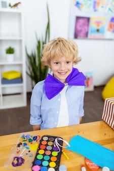 Fröhlicher junge. fröhlicher junge, der lächelt, während er eine papierschleife trägt, die in der nähe des tisches mit wasserfarbe steht