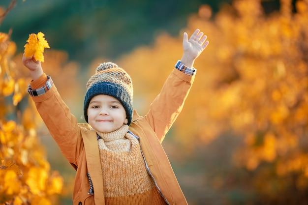 Fröhlicher junge herbst geht in den garten mit bäumen in gelben blättern