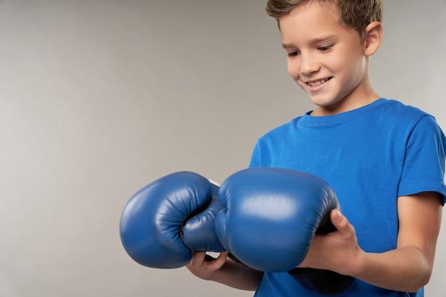 Fröhlicher junge im blauen hemd mit boxhandschuhen