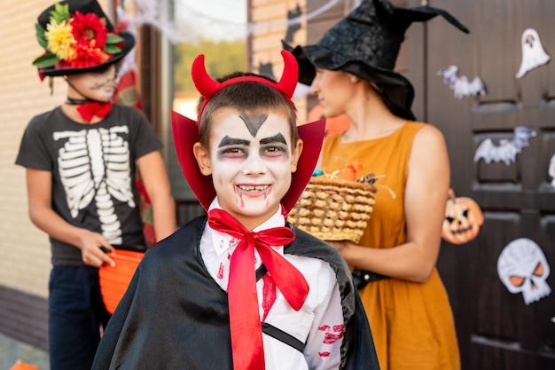 Fröhlicher junge im halloween-kostüm, der sie gegen junge frau im gelben kleid und im hut hält korb mit leckereien und seinem freund betrachtet