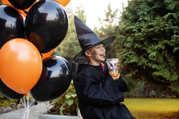 Fröhlicher junge im kostüm hält an halloween saft in der nähe von ballons