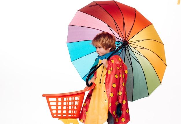 Fröhlicher junge im regenmantel mit buntem regenschirm. wolkenregenschirm. netter kleiner kinderjunge, der in herbstkleidung trägt