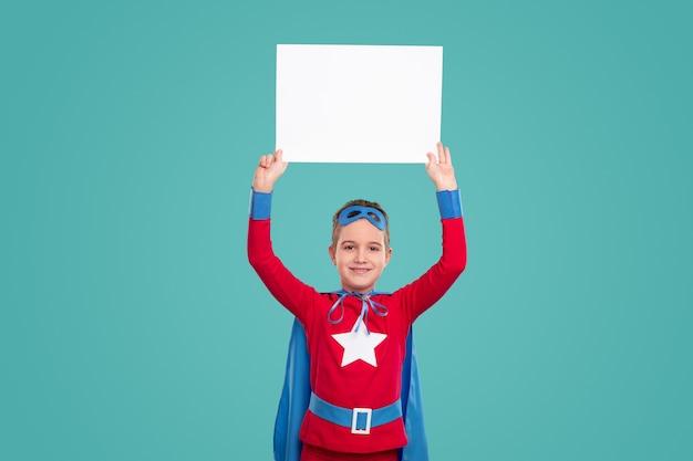 Fröhlicher junge im superheldenkostüm, der leeres plakat in erhobenen armen gegen türkis hält