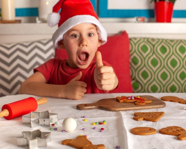 Fröhlicher junge im weihnachtsmann-hut macht lebkuchenweihnachtsabend