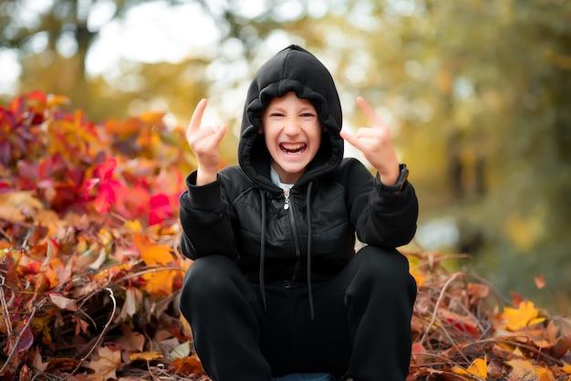 Fröhlicher junge in schwarzer kleidung sitzt an der grenze vor dem hintergrund eines herbstbusches und zeigt gesten