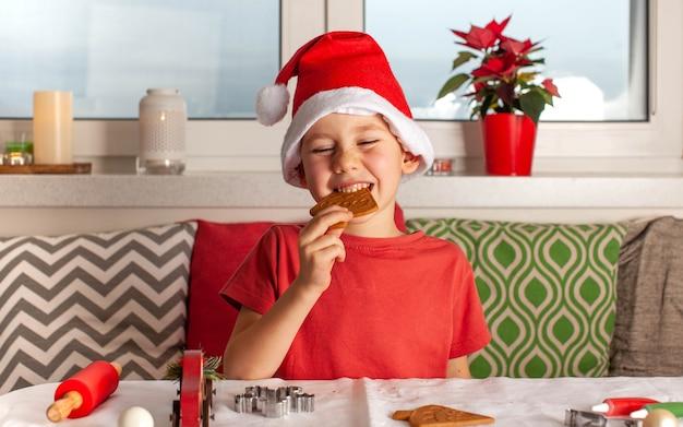 Fröhlicher junge in weihnachtsmann-hut isst weihnachtslebkuchen, der neujahrslebkuchen kocht