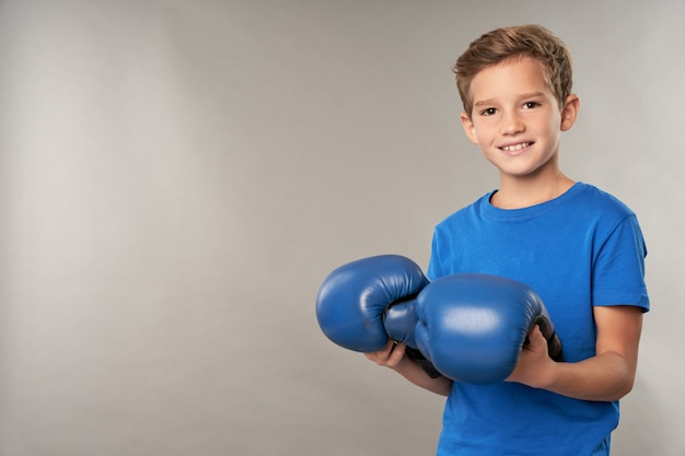 Fröhlicher junge mit boxhandschuhen, die vor grauem hintergrund stehen
