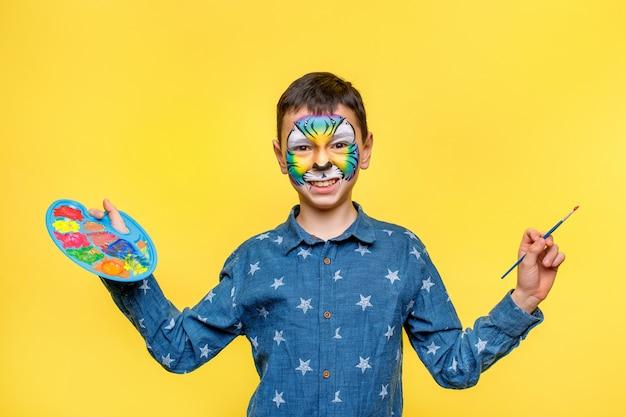 Fröhlicher junge mit farbe auf geburtstagsfeier, bunter tiger, der palette mit gouache isoliert auf gelber wand hält.