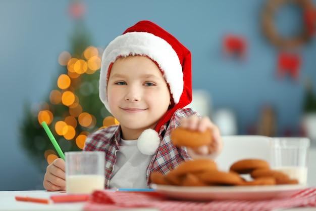 Fröhlicher junge schreibt einen brief an den weihnachtsmann, nahaufnahme,
