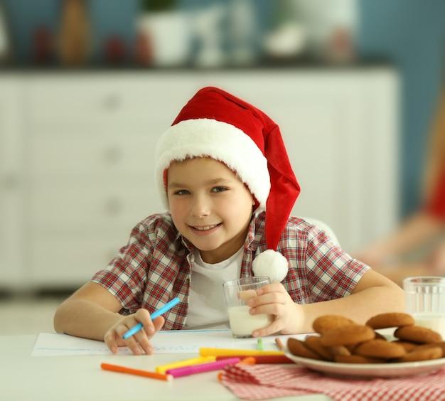 Fröhlicher junge schreibt einen brief an den weihnachtsmann, nahaufnahme