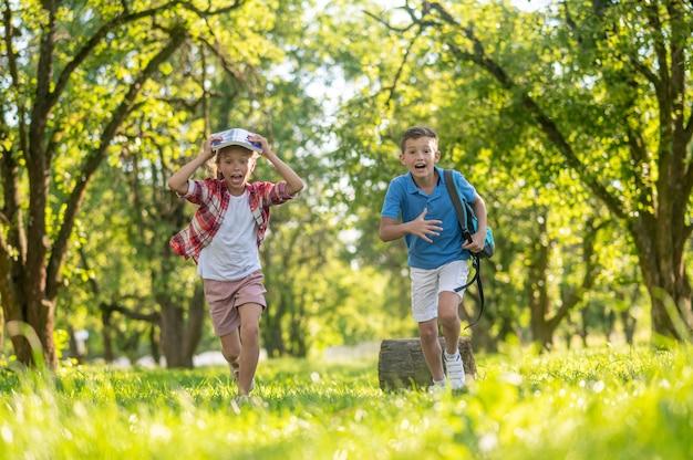 Fröhlicher junge und mädchen, die im park laufen