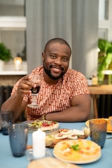 Fröhlicher junger afrikaner, der sich mit einem glas rotwein vor der kamera aufheitert, während er während des weihnachtsessens am festlichen tisch sitzt