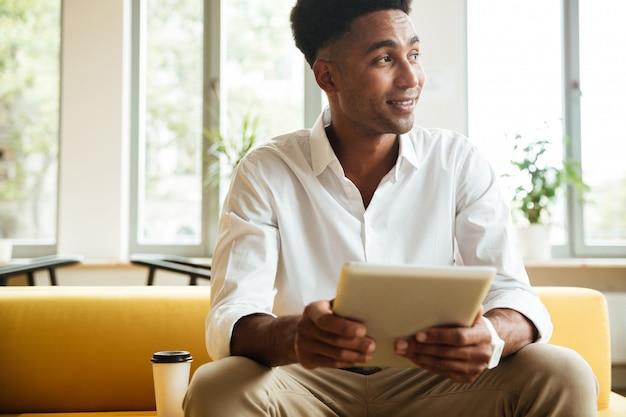 Fröhlicher junger afrikanischer mann, der coworking sitzt