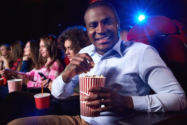 Fröhlicher junger afrikanischer mann, der lächelt und seinen popcorn-eimer hält, der einen film am lokalen kino-copyspace genießt, snacks glücksunterhaltung positivität freizeitaktivitätskonzept.