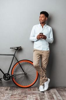 Fröhlicher junger afrikanischer mann, der per telefon plaudert.