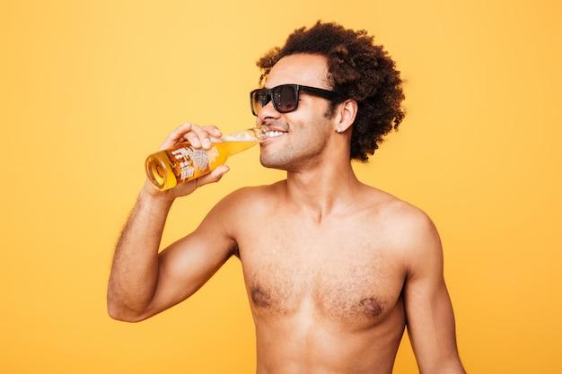 Fröhlicher junger afrikanischer mann, der trinkendes bier steht.