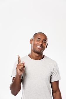 Fröhlicher junger afrikanischer mann, der zeigt.