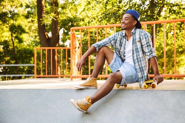 Fröhlicher junger afrikanischer mann mit skateboard